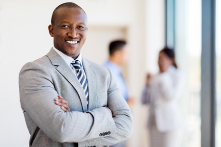 african business man: successful african business man with arms folded in modern office