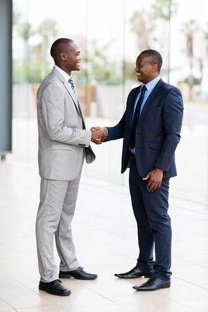 african american handshake: successful african businessmen handshaking in conference hall
