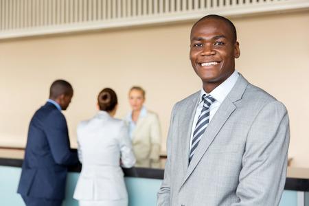 ホテルのフロントに立っているハンサムなアフリカ系アメリカ人マネージャー