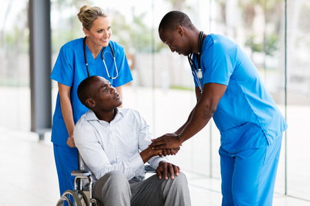 health professional: friendly male medical doctor handshaking with handicapped patient Stock Photo
