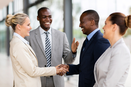 group cooperation: happy african man introducing businesswoman to business partners Stock Photo