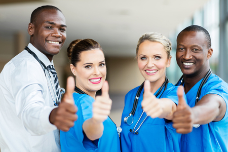 group of modern healthcare workers thumbs up. Stock Photo