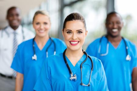 happy nurse: pretty medical nurse and colleagues in hospital