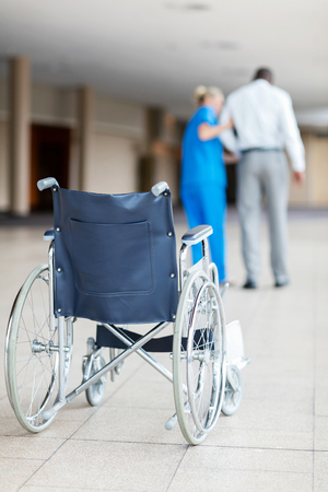 wheelchair woman: rear view of nurse helping patient walk with wheelchair in foreground