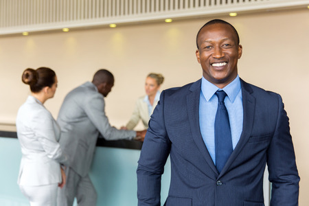 portrait of happy african businessman standing at hotel reception