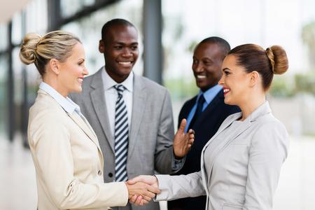 african american handshake: cheerful business team welcoming businesswoman Stock Photo