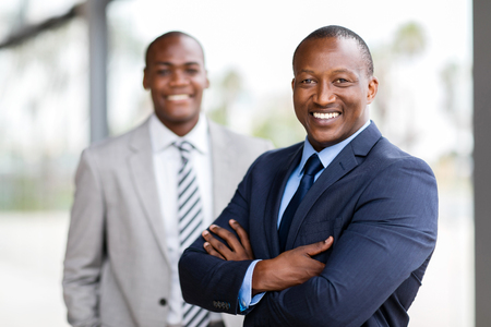 business men: cheerful african businessman standing in front of colleague
