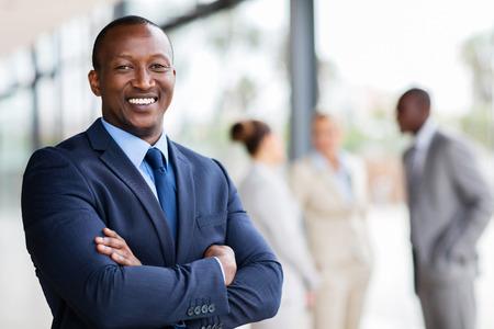 Retrato do trabalhador de escritório africano bem sucedido com os braços cruzados