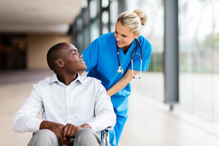 discapacitados: enfermera de sexo femenino que cuida habla con el paciente en el hospital con discapacidad