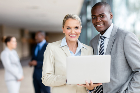middle aged businesswoman with african businessman using laptop in office