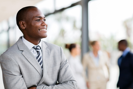 colleagues: young african male corporate worker daydreaming in office