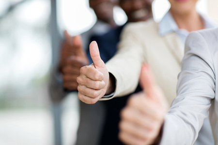 closeup of business people giving thumbs up Foto de archivo