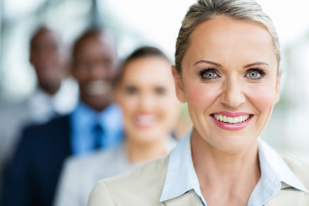 portrait of pretty mid age businesswoman with colleagues standing in a row Stockfoto
