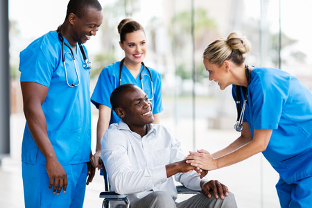 happy female doctor greeting disabled patient in hospital