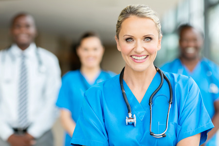 attractive middle aged healthcare worker with colleagues on background Stockfoto