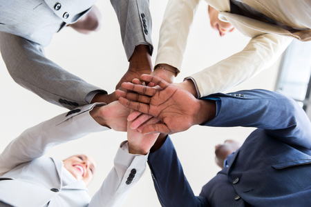 team hands: underneath view of business people hands together
