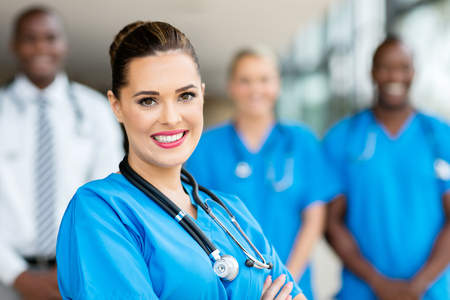 Caucasian woman: attractive young medical doctor and colleagues in hospital Stock Photo
