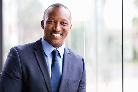 business men: cheerful african business man standing by office window Stock Photo