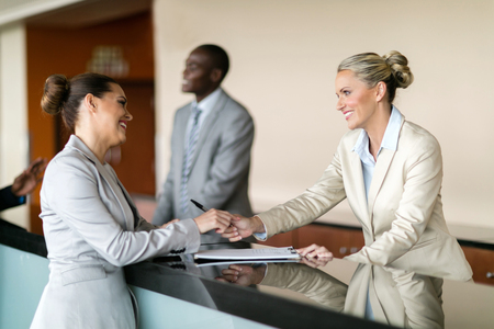counter service: businessman check in at hotel reception Stock Photo