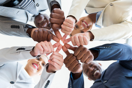 low angle view of multiracial co-workers with thumbs joined together