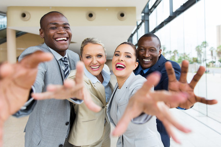 group of cheerful multiracial businesspeople reaching for the camera Standard-Bild