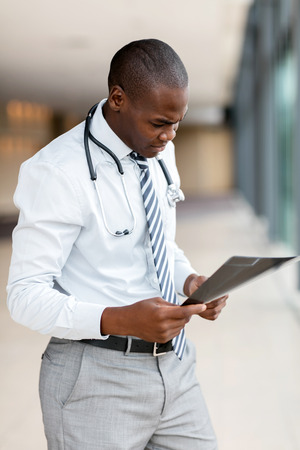 modern african american doctor looking at x-ray in office