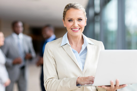 portrait of happy mature businesswoman using laptop computer
