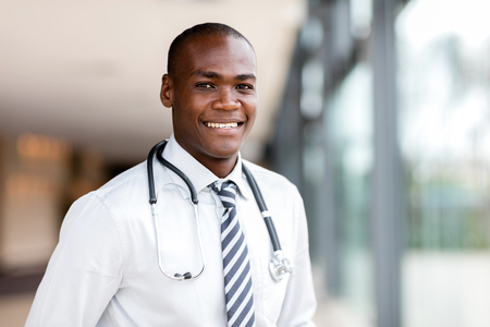 cheerful young african medical doctor at hospital