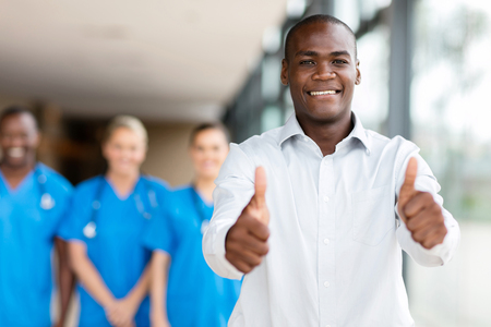 happy african man giving thumbs up in front of medical group