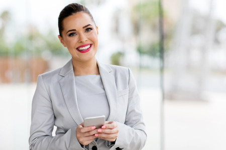 beautiful young career woman using cell phone in office