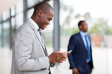african businessman using smart phone in modern office