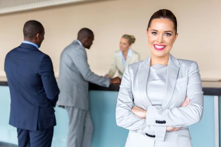 Szczęśliwa młoda businesswoman stojących w recepcji hotelowej