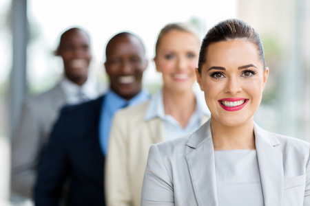 smiling young businesswoman with colleagues standing in a row Stockfoto