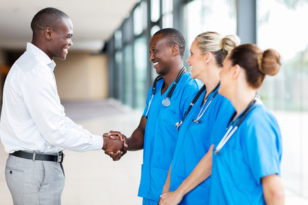 happy medical rep handshaking with group of doctors in hospital Stockfoto