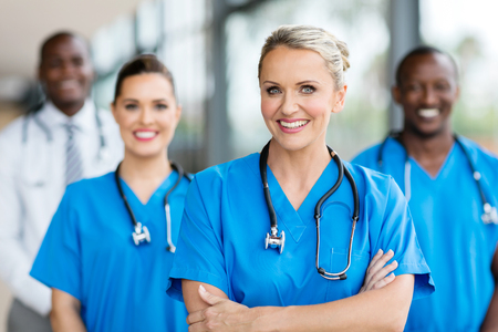 pretty female medical doctor with colleagues in background