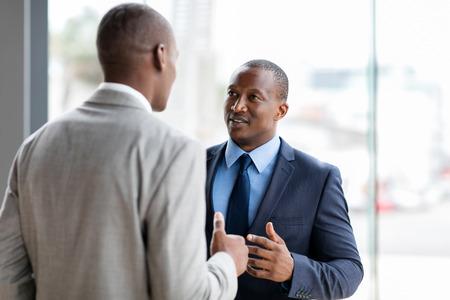 men talking: successful african american businessmen having conversation in office