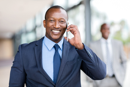 cheerful african businessman talking on cell phone in office Standard-Bild