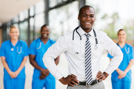 handsome african american medical doctor with colleagues in background