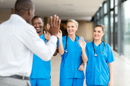 rear view of patient waving goodbye to friendly medical team