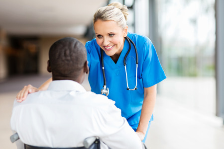 pretty female doctor comforting disabled patient in wheelchair Stockfoto