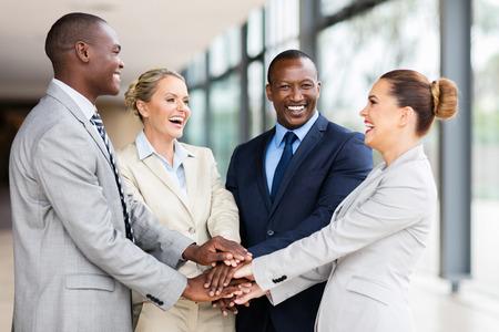 mujeres juntas: alegre Equipo de negocios multirracial que pone sus manos juntas Foto de archivo