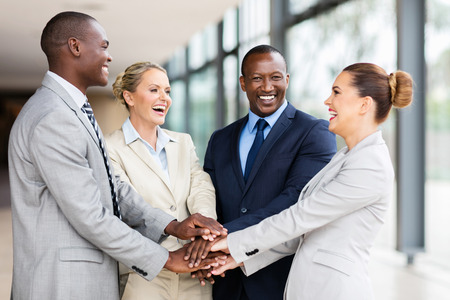 teamwork business: cheerful multiracial business team putting their hands together