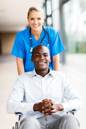 medico con paciente: Retrato de la enfermera bastante médica con el paciente masculino en silla de ruedas