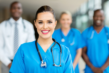 portrait of beautiful young female doctor standing with co-workers