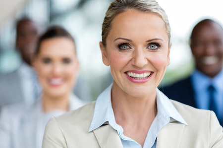 portrait of happy mature businesswoman in front of colleagues