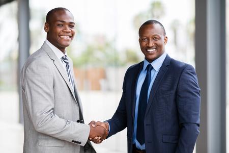 portrait of happy african american businesspeople handshaking