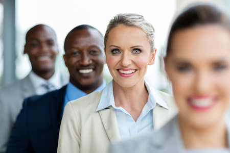 happy mid age businesswoman standing in a row with business team Stockfoto