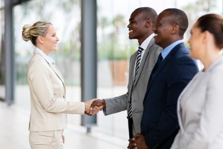 middle aged businesswoman handshaking with group of employees in office