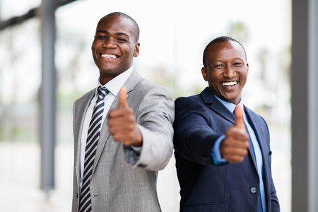 african business: cheerful african business team giving thumbs up Stock Photo