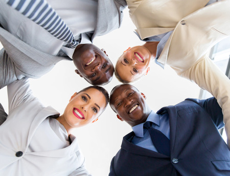 underneath view of business team in a circle looking down
